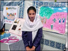 A Pakistani girl stands next to her painting during a painting contest at her school in Mingora on 19 Sept 2009