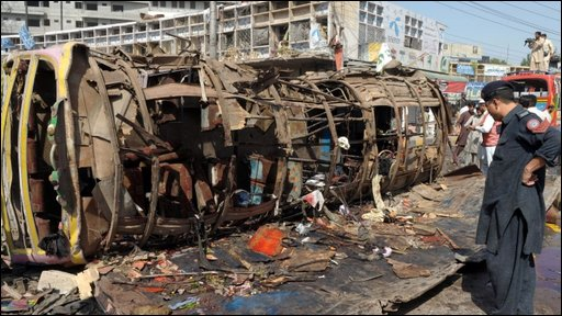 Pakistani policeman looks at bus wreckage