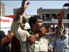 Pakistani men mourn the death of their relatives at the site of a suicide car bomb blast in Peshawar on October 9, 2009.