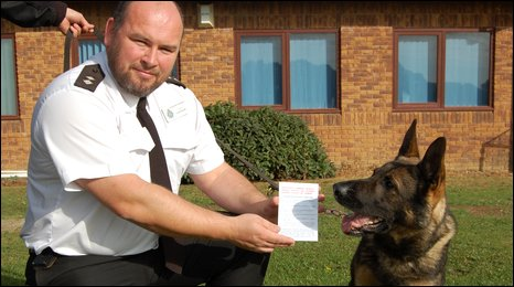 Inspector Luke Russel holding one of the cards, next to a police dog