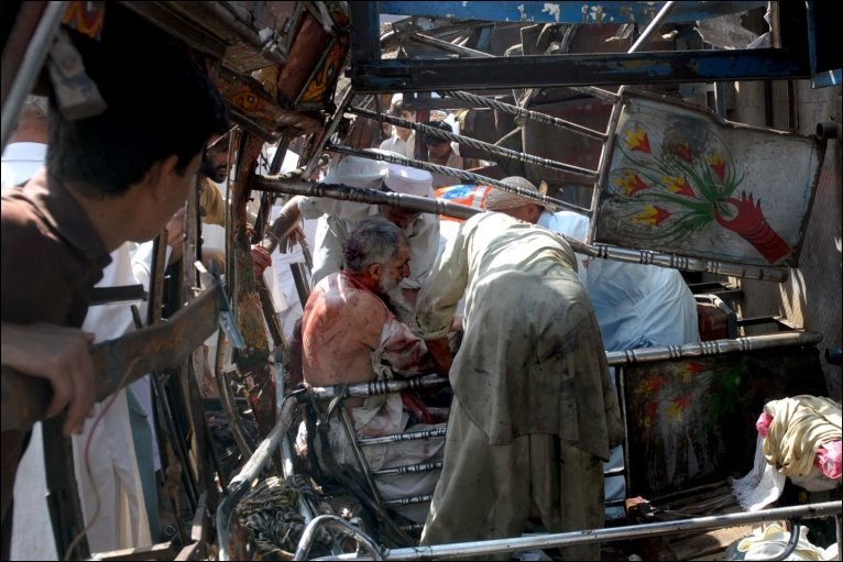 Pakistani bystanders remove an injured bomb blast victim