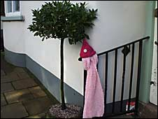 Pink pixie hat and scarf on railing in Hatherleigh