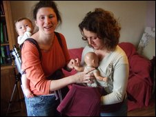 Rebecca, a doula, teaching Daniela  how to use a sling baby carrier