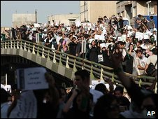 Iranian opposition protesters march over a bridge in Tehran