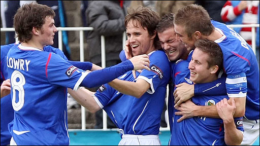 Hat-trick hero Paul Munster is mobbed by his Linfield team-mates at Seaview