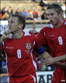 Craig Bellamy celebrates Wales' leveller by silencing the home crowd