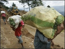Bundles of food are carried across a stretch of road buried by a landslide in Tublay town, Benguet province - 13 October 2009