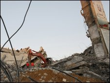 Palestinian workers clear rubble at parliament building in Gaza, bombed by Israel in January
