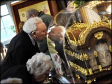 A elderly man leans forward to kiss the case containing the Relics of St. Therese of Liseux at St. Teresa of Liseaux church in Taunton