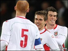 Aaron Ramsey (centre) is congratulated as his first international goal seals victory