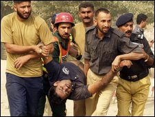 Pakistani police remove an injured colleague from a police academy in Lahore on 15 October 2009