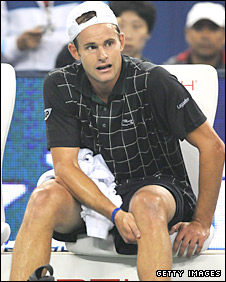 Andy Roddick waits for attention to his knee