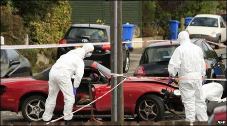 Forensic scientists examine the bomb damage to the car