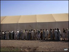 Pakistani tribal families who have been displaced from Bajur and Mohamand regions due to fighting between security forces and Taliban militants, wait to receive food relief at Jalozai camp in Peshawar, Pakistan on Thursday, Sept. 17, 2009.