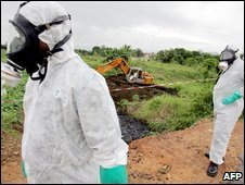 Two civil protection workers pass by a bulldozer clearing a site polluted with toxic waste at the Akouedo district in Abidjan