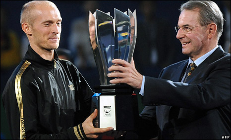 Nikolay Davydenko is presented with the Shanghai Masters trophy by International Olympic Committee President Jacques Rogge