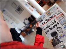 A person looks at news from a local paper in Maubeuge, northern France, on October 17, 2009, about Eugene Rwamucyo, employed as a doctor for staff at the Maubeuge hospital who was suspended