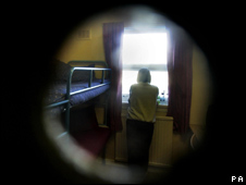View of a woman prisoner in her jail cell through the cell door window