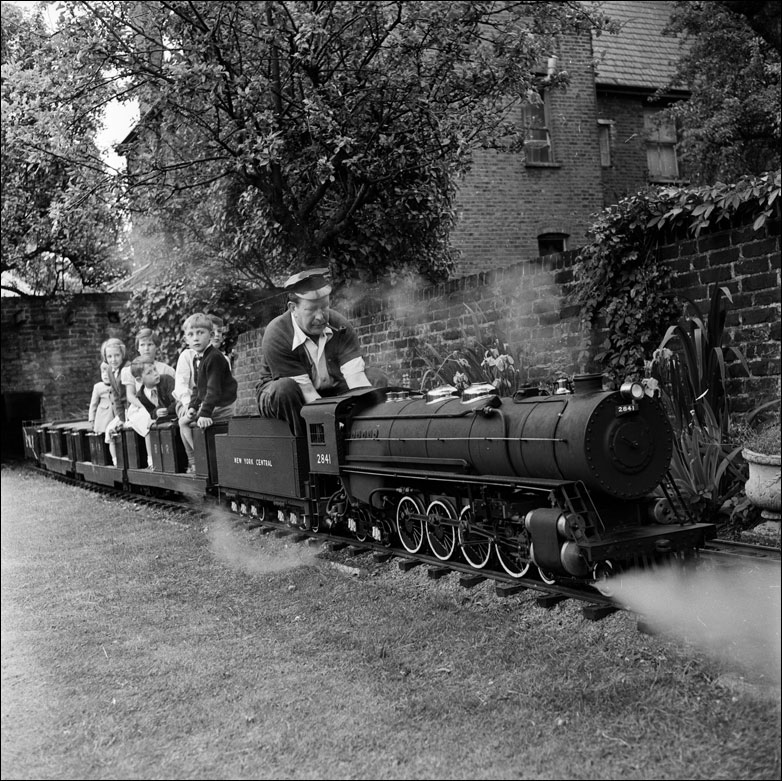 London bank manager George Scanner takes a group of children on a ride around his garden on a miniature steam engine