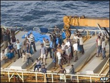 Suspected illegal migrants stand on the Ocean Lady