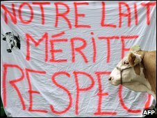 "A cow stands in front of a banner (which reads: ""Our milk deserves respect"") during a demonstration of farmers in eastern France, 16 October 2009"