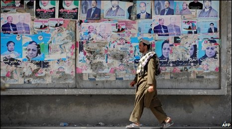 An Afghan pedestrian walks in front of a wall of torn posters of presidential and provincial candidates in Kabul on September 24, 2009.
