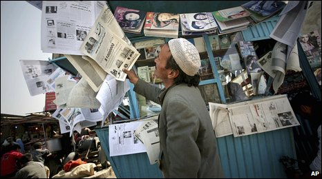 Man in Kabul reads newspaper on street stall (20 Oct 2009)