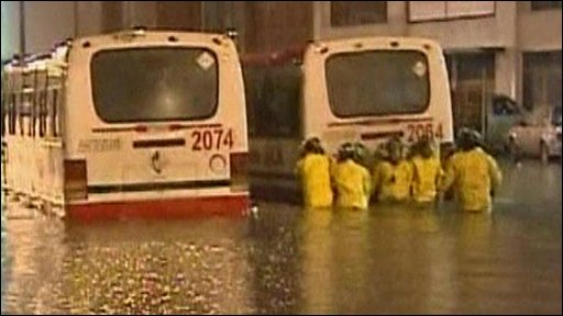 Emergency workers pushing bus out of flood water
