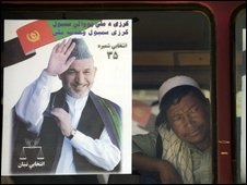 An Afghan man peers trough the window of a bus decorated with electoral posters
