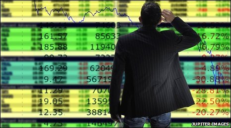 Trader standing in front of share price monitor. [Posed by actor]