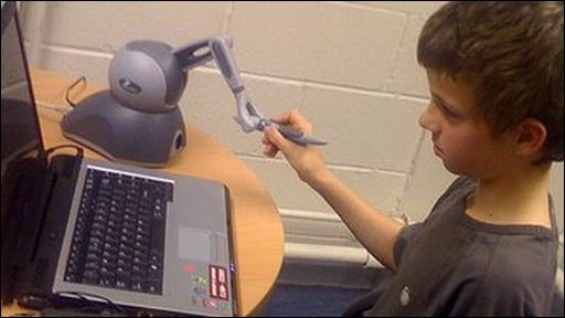 Tom on his computer and robotic arm