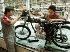 Workers in a motorbike factory
