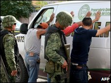 Mexican soldiers frisk suspects near the scene of a murder in Juarez