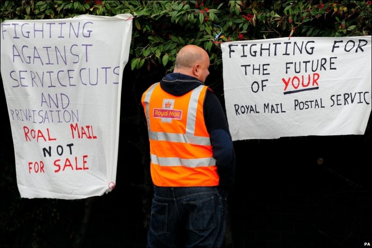A striking postal worker with banners in Coventry