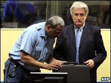 Security guard opens the briefcase of former Bosnian Serb leader Radovan Karadzic (right) in the Hague, file pic from March 2009.