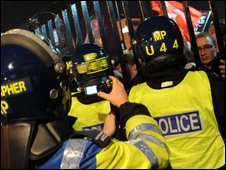 Police photographers film protesters at the BBC gates