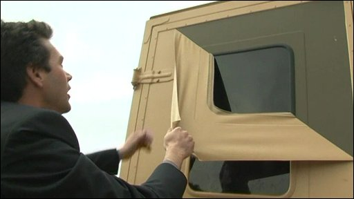 Steve Mitchell peels a layer of paint off a military vehicle