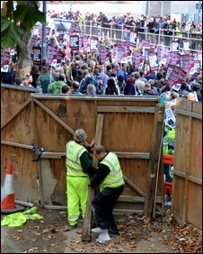 Two workmen on Wood Lane did their best to keep protesters at bay