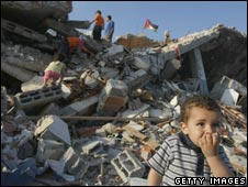 Gaza child stands in front of his family home that was destroyed during Israel's campaign