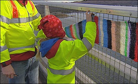 Volunteers attaching knitting to Skye bridge