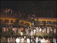 Egyptians gather around the site of a collision between two passenger trains in Girzah district, Egypt