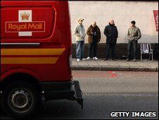 Royal Mail van drives past postal workers forming a picket line