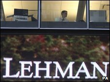 A man looks out the window at the Lehman Brothers headquarters in New York