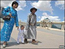 Couple in traditional dress walk through Ulan Bator square