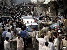 People make a way for ambulance to collect injured people at the site of explosion in Peshawar
