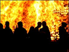 People standing in front of a bonfire