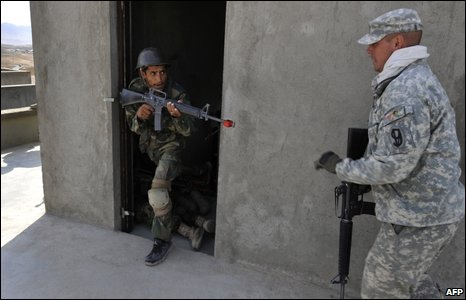 A US Army trainer (R) guides an Afghan soldier during combat training at The Afghan National Army (ANA) training camp on the outskirts of Kabul (September 27, 2009)