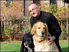 Father Peter Needham with his two dogs, Mary, left and Joseph