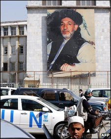 UN vehicle drives past a poster of Hamid Karzai