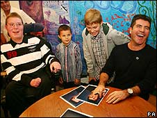 Simon Cowell (right) signing autographs for children
